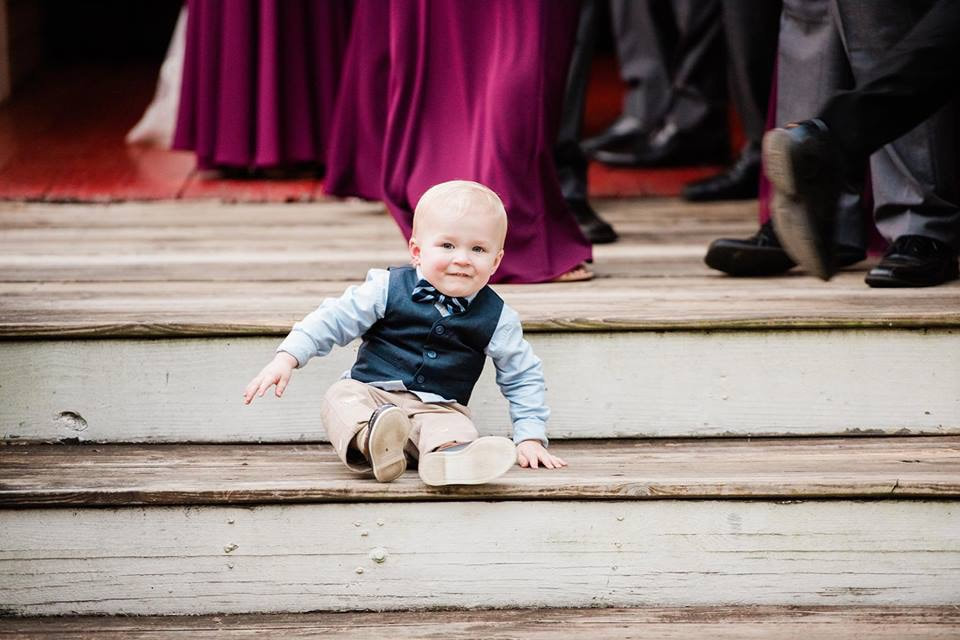 toddler boy in vest on farmhouse steps during processional line up
