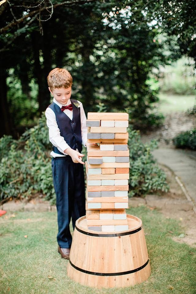 ring bearer in navy tux playing giant Jenga at outdoor wedding