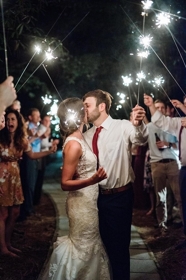 husband and wife kissing while holding sparklers during grand exit