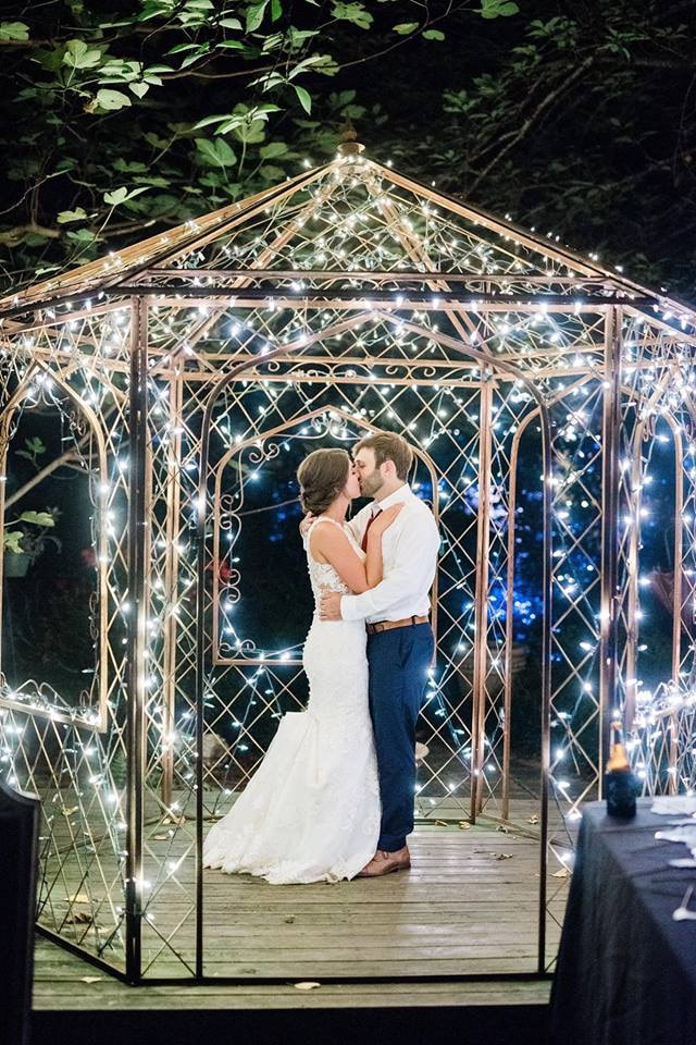 newly married couple kissing under night lights in gazebo