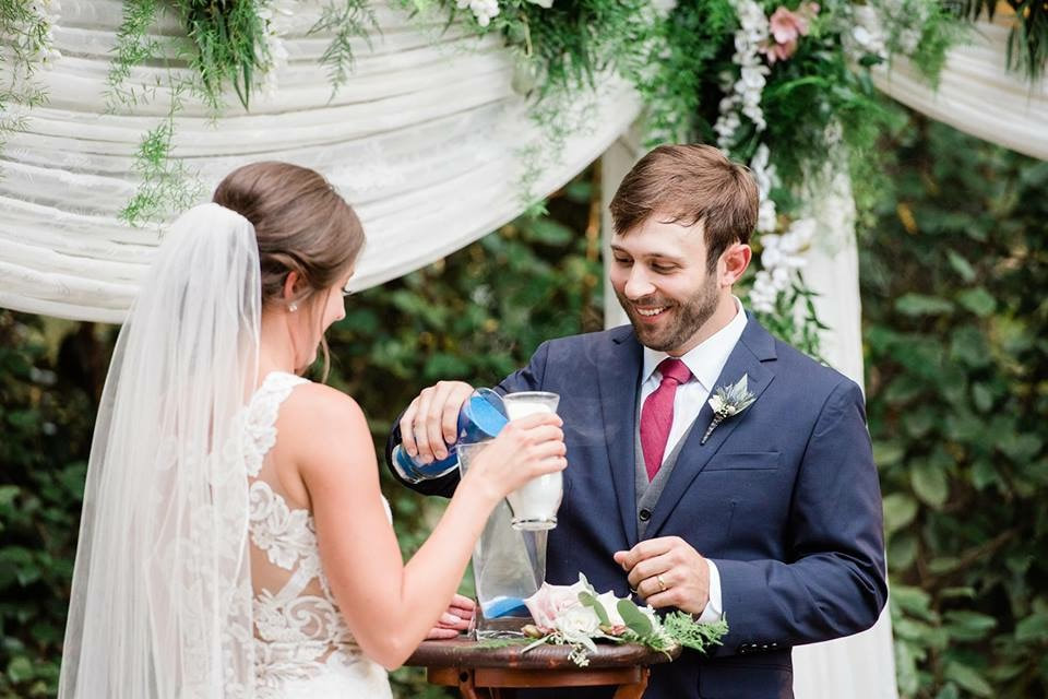 bride pouring white sand and groom pouring blue sand into vase during sand ceremony