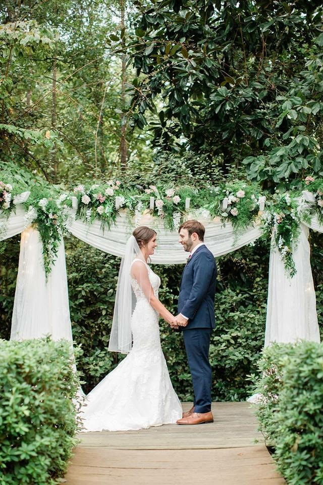 bride and groom holding hands by altar covered in white chiffon and cascading greenery with white and soft pink flowers