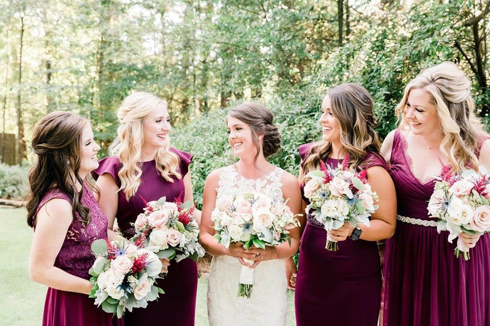 bridesmaids in wine bridesmaids dresses holding bouquets with white and light pink flowers and burgundy berries