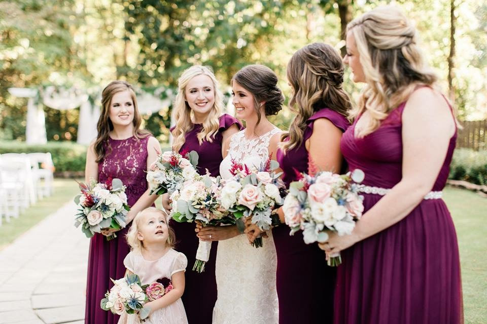 bride with bridesmaids in cab colored dresses and flower girl all holding bouquets