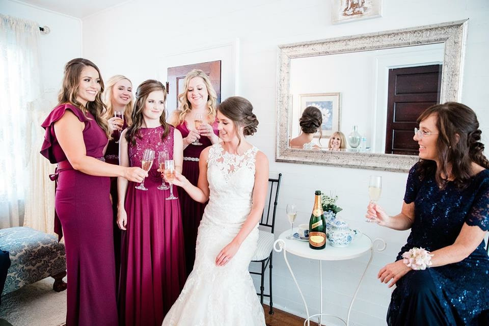 bride and bridal party clinking champagne glasses while getting ready for the big day