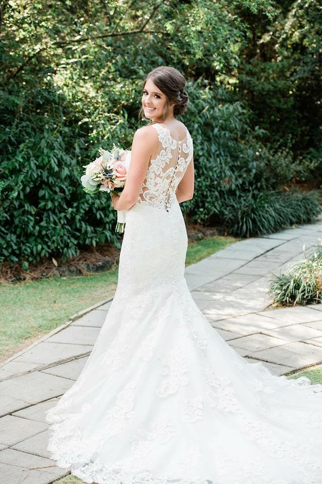 bride in lacy, mermaid shaped dress with buttoned back