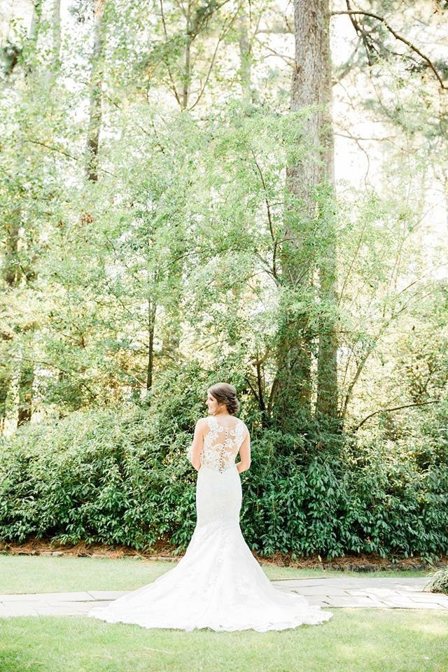 bride posing for photo in woods with laced-back wedding dress