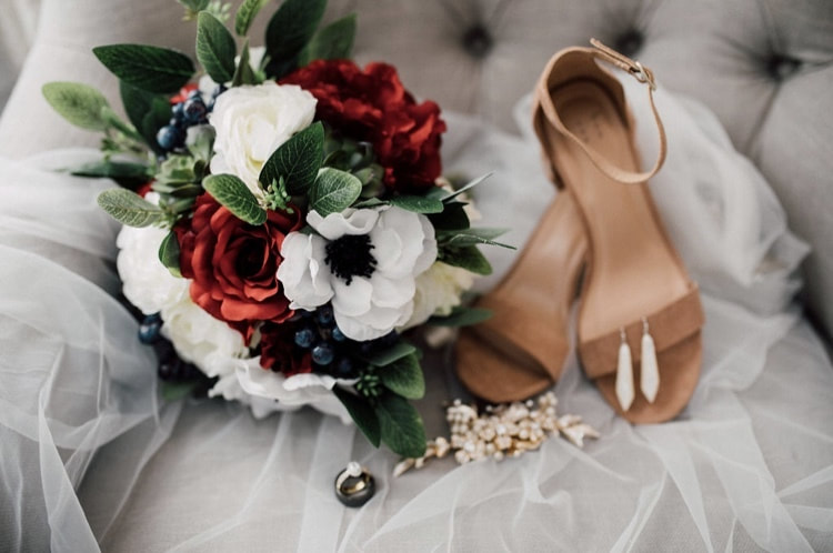detail photo with brides heels, jewelry, wedding rings, veil, and bouquet of red and white flowers and blue berries