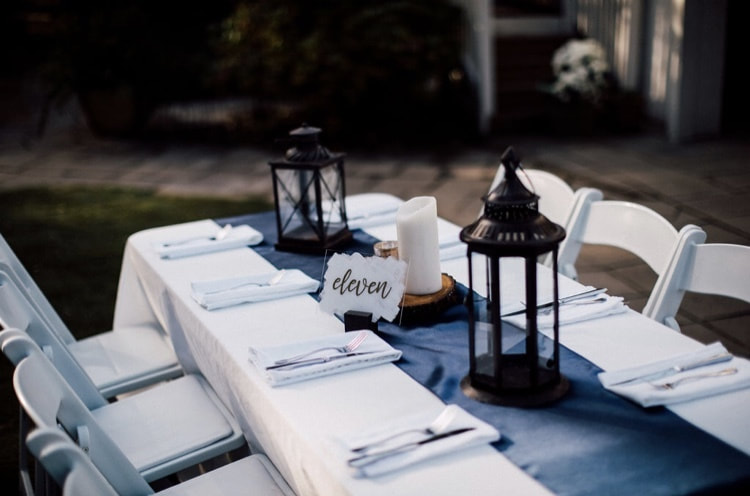 guest table setup with satin navy runners, wood slice and candles, and black lanterns
