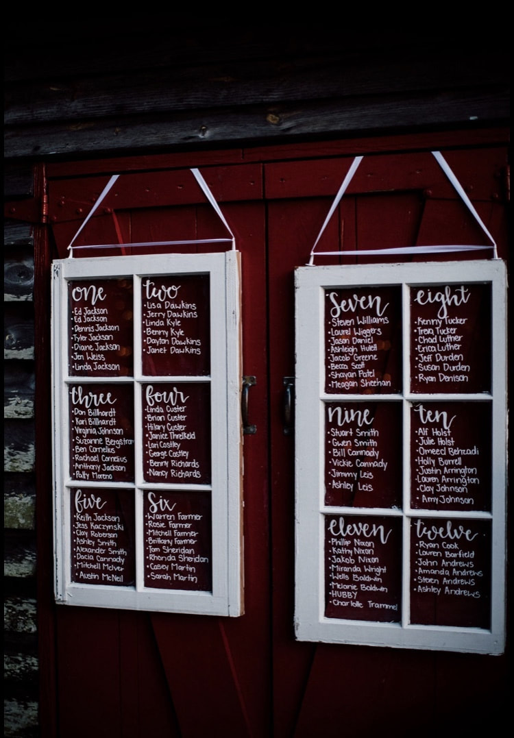 assigned seating charts on white window panes against smokehouse red barn doors