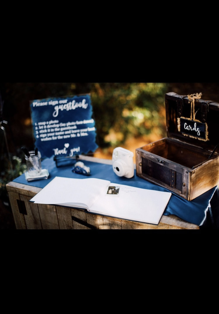 guestbook table with navy blue runner, brown card box, and Polaroid camera