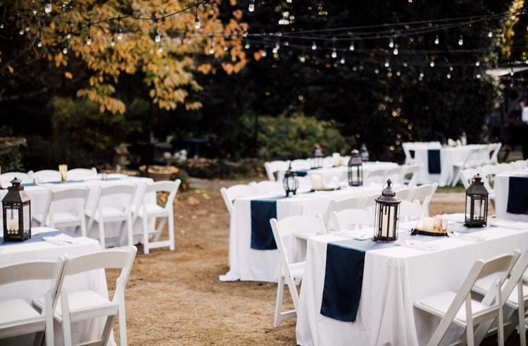 simple fall outdoor wedding guest table setup with white chairs and table clothes, navy runners, black lanterns and wood slices with candles on top