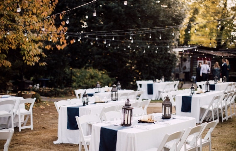 fall outdoor wedding with changing leaves, golden light, string lights, and rectangle guest tables with rustic decor