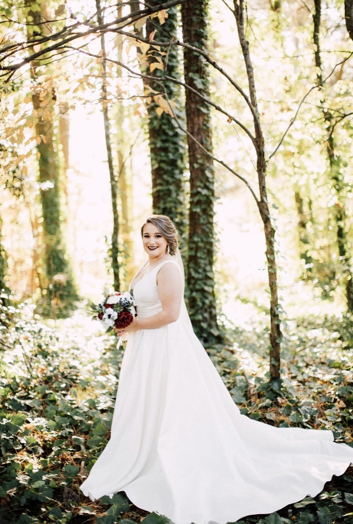 bride holding red, white and blue bouquet posing in the woods during golden hour
