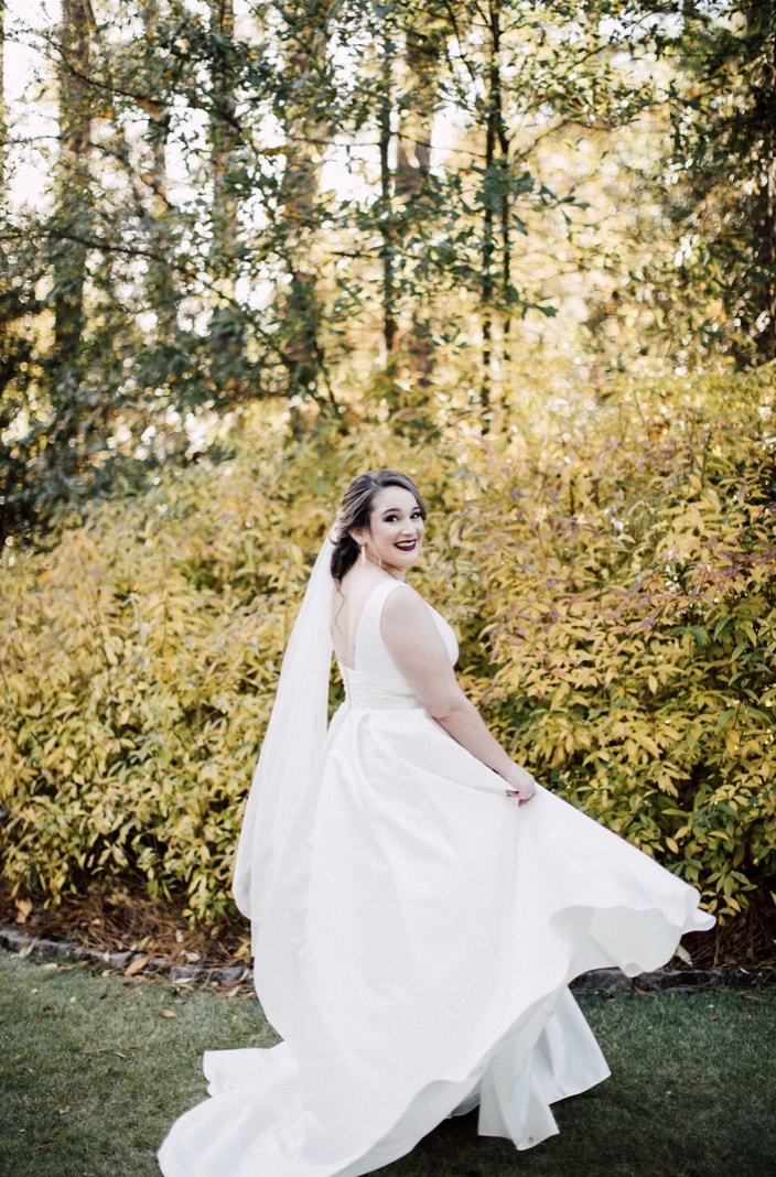 bride twirling elegant wedding dress while looking back at camera surrounded by green and yellow bushes