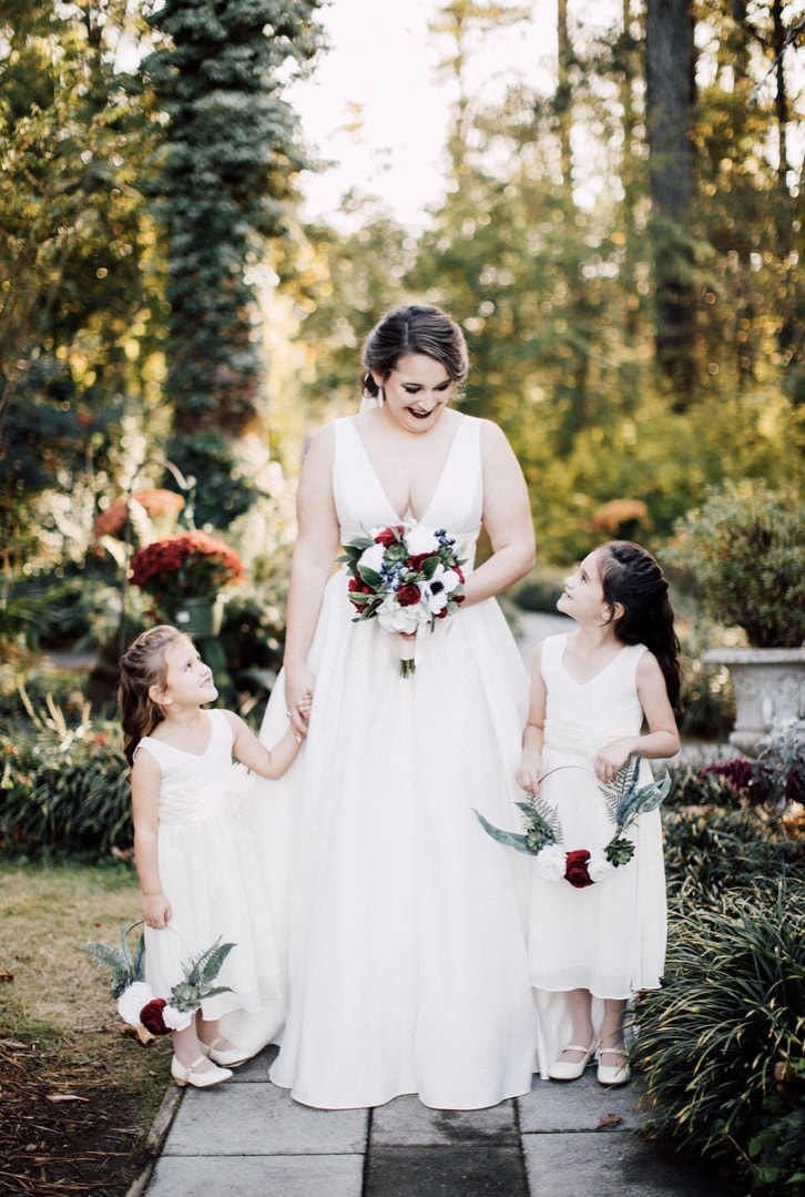bride holding red, white and blue bouquet posing with flower girls