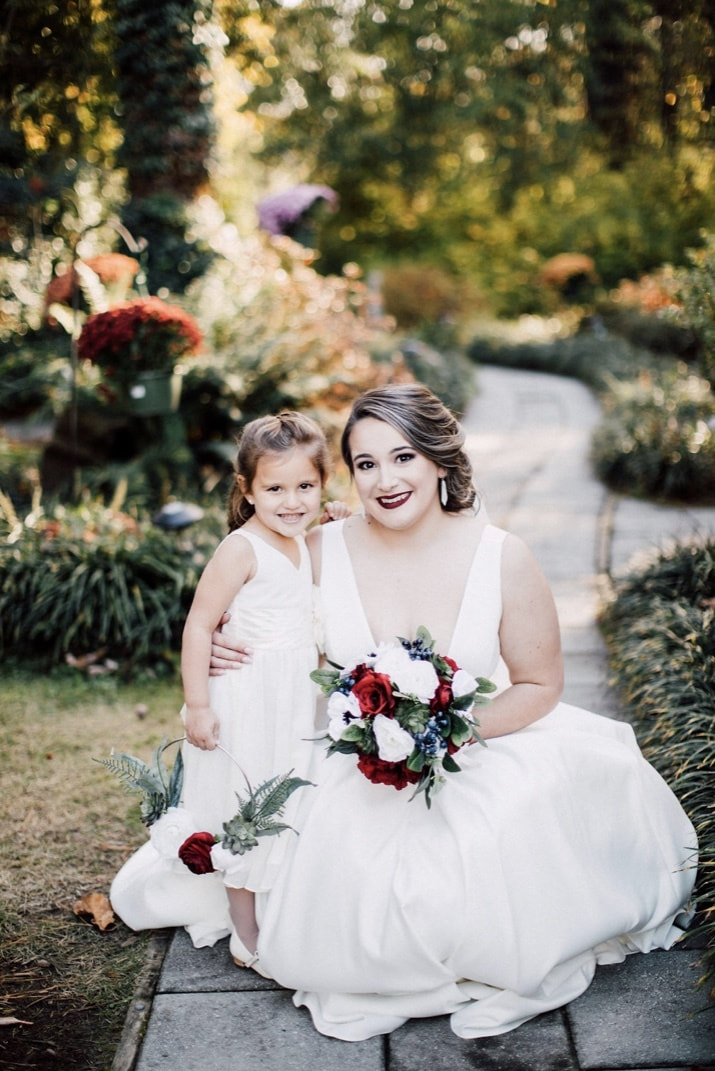 bride holding bouquet of red, white and blue flowers posing with flower girl holding flower basket