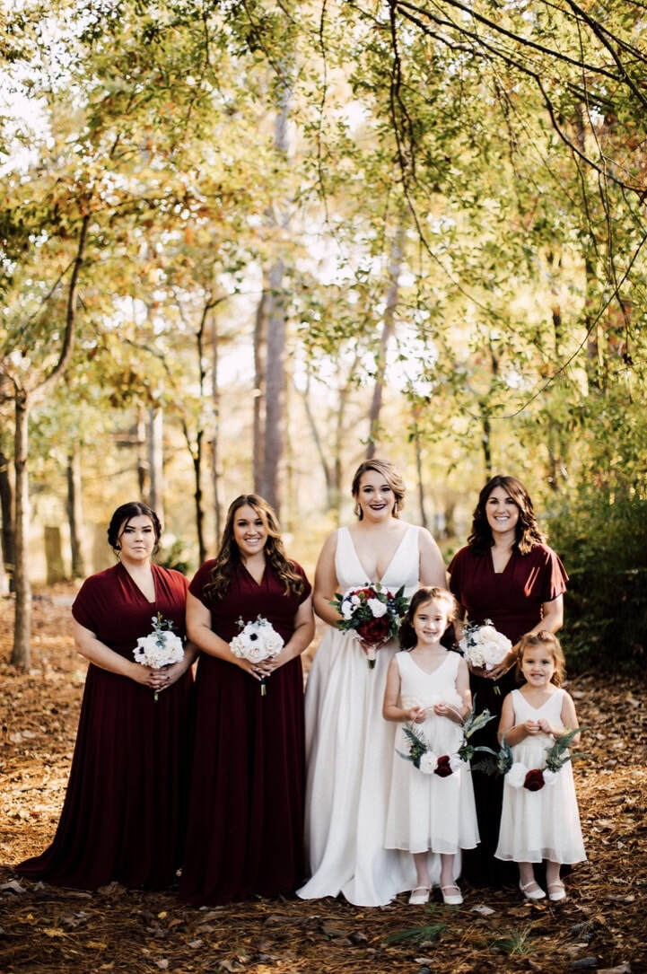 bride with bridesmaids in wine colored dresses holding white bouquets, and with flower girls holding flower baskets