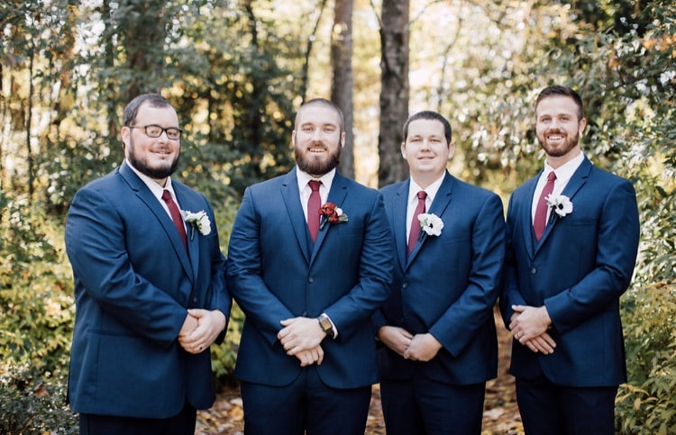 groom and groomsmen in navy suits with deep red ties and white and red boutonnieres