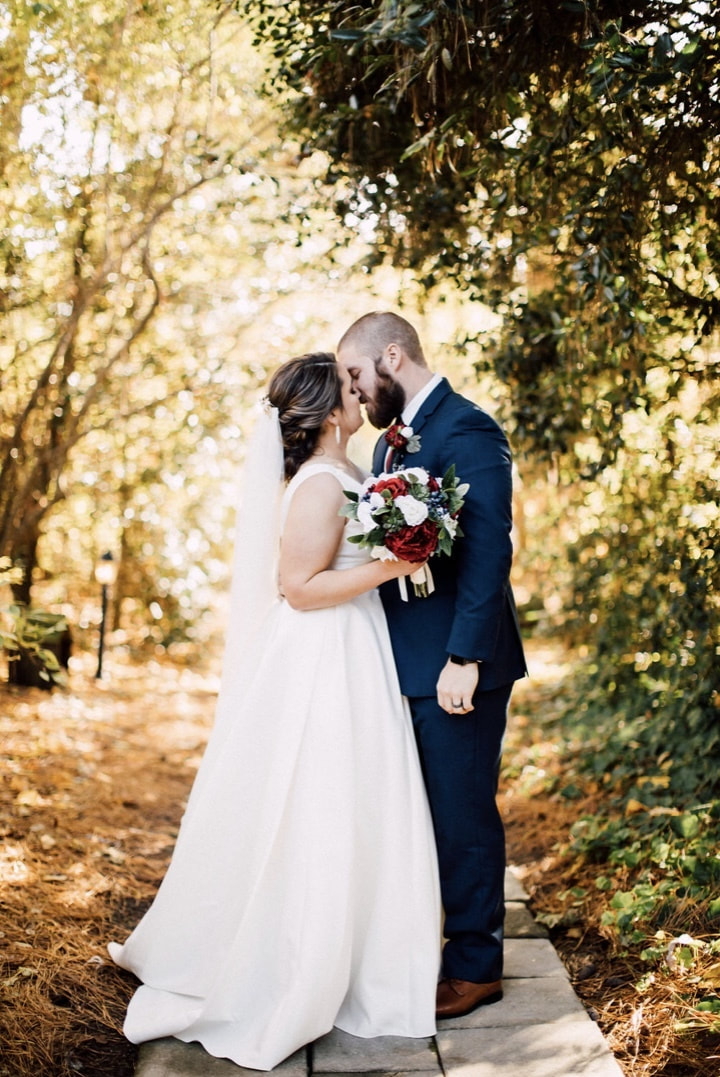 newlyweds almost kissing surrounded by trees with golden light