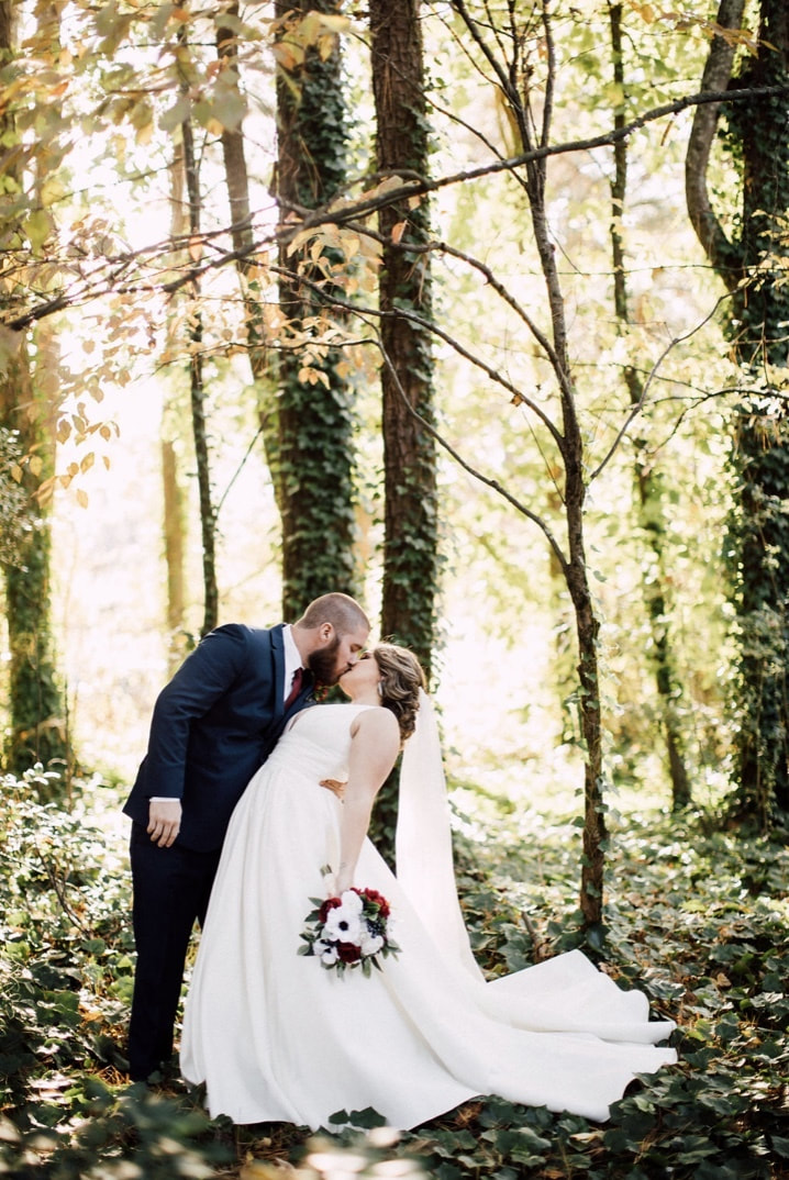 husband dipping wife for kiss during post-ceremony photos in woods during fall