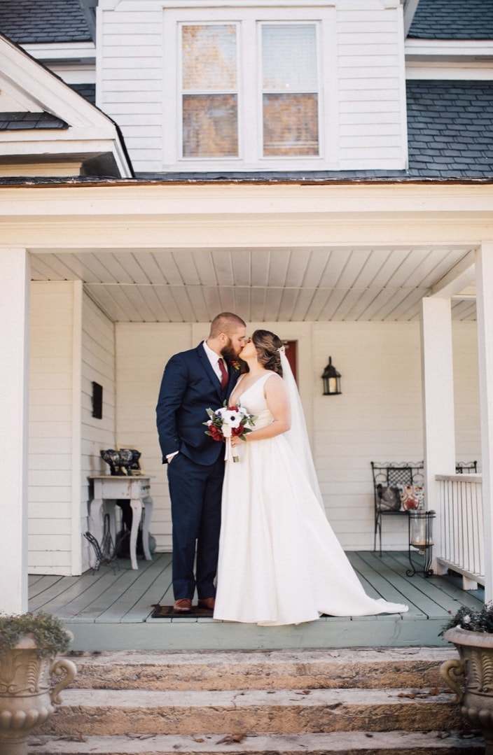 newlyweds kissing on Four Oaks Manor's front porch