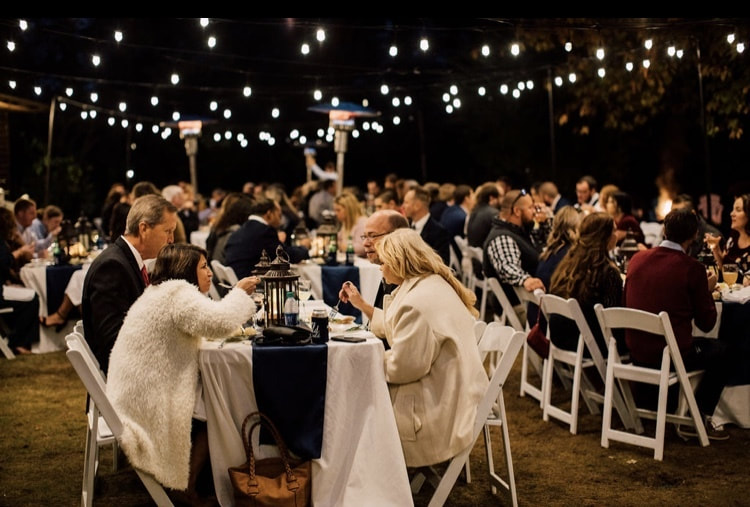 guests eating during outdoor fall reception with heaters