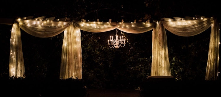 chandelier and lights on at Four Oaks' outdoor arbor during fall night