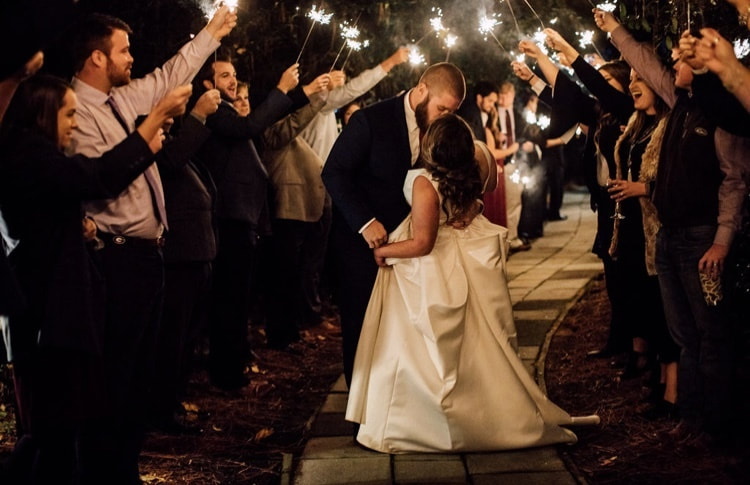 groom dips bride for kiss while guests wave sparklers for grand exit