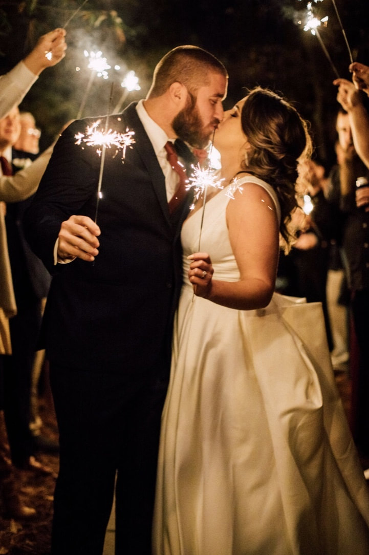 bride and groom kissing holding sparklers during grand send off