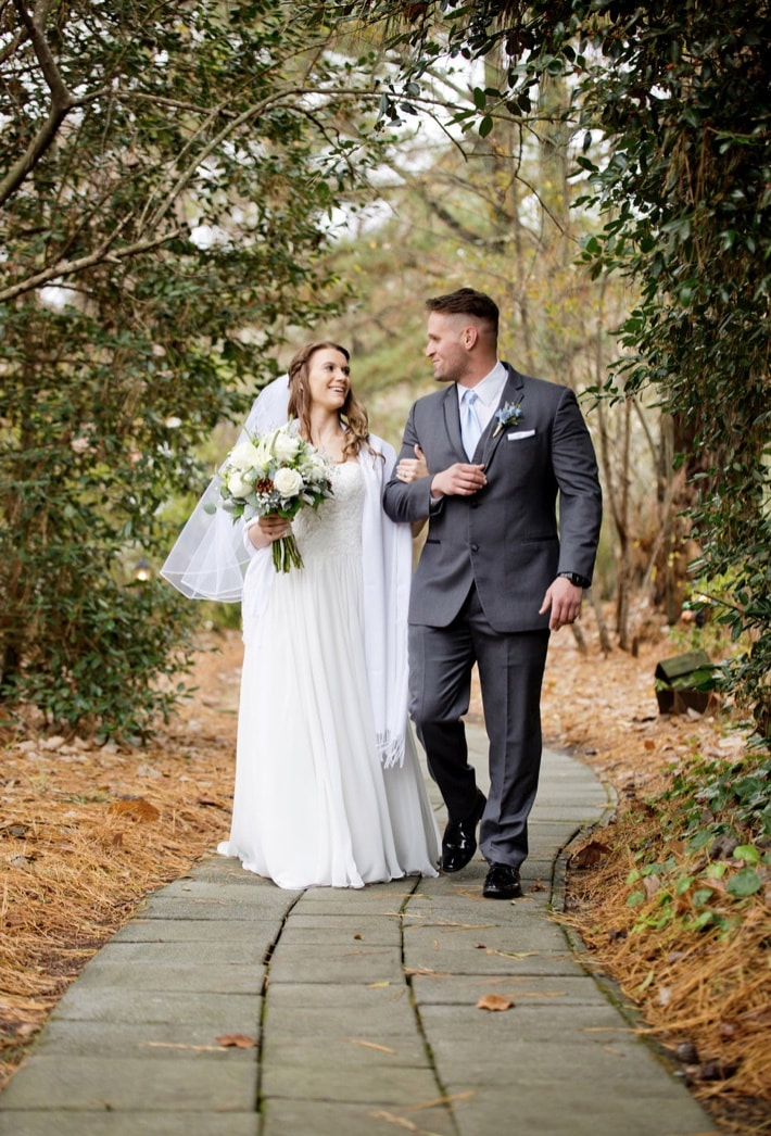 bride and groom walk down winding path arm in arm