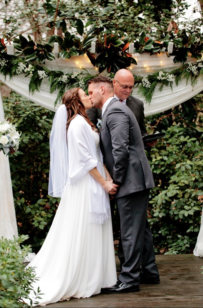 bride and groom kissing at winter decorated altar