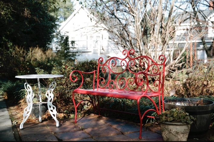 Four Oaks Manor's red bench and white table