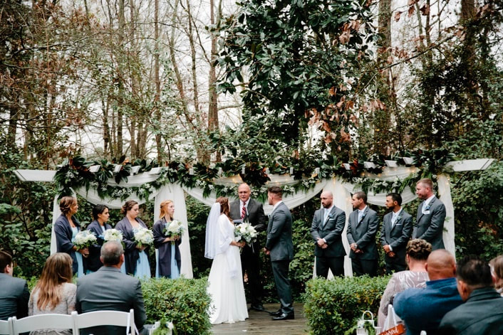 outdoor winter ceremony at greenery decorated altar