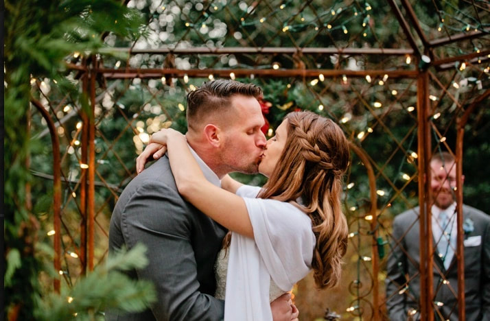 bride and groom kiss during first dance in gazebo