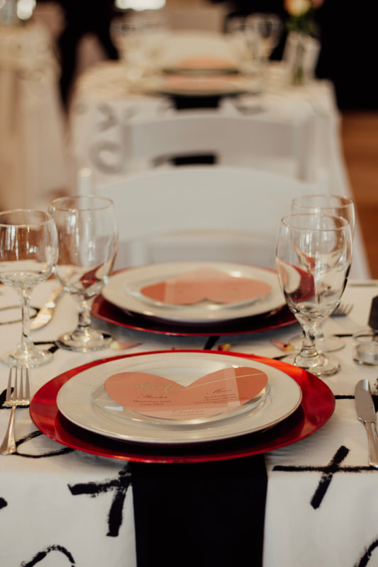 Valentines table setting with red chargers and heart shaped menus