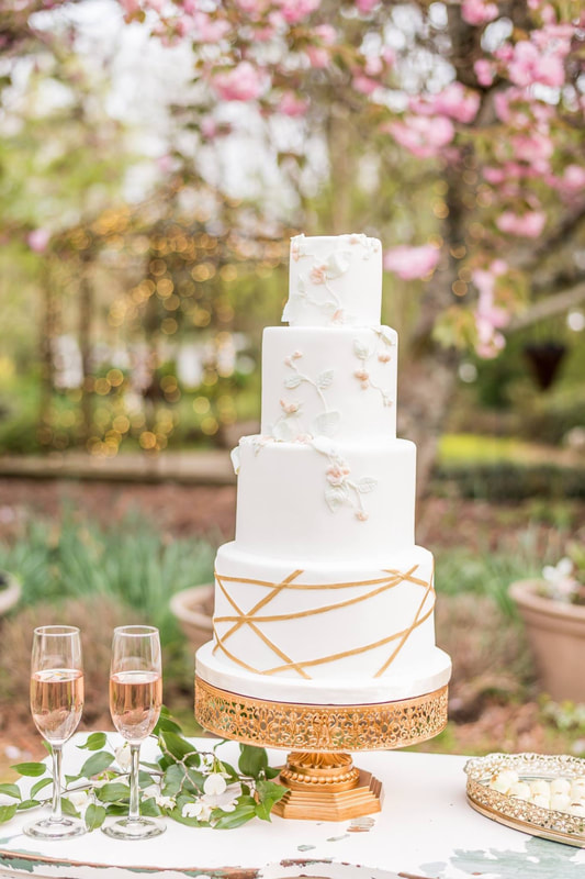white tiered wedding cake with geometric shapes and flower details