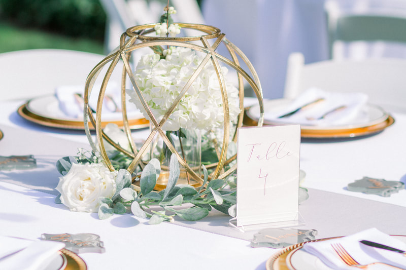table centerpieces of white flowers, greenery, gold geometric shapes, and table numbers