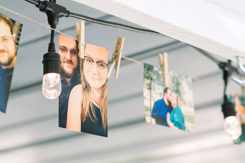 couple photos hanging from twine and string lights at Four Oaks Manor's covered porch