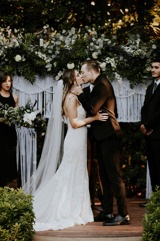 couple kissing at altar with white macramé and floral arrangement
