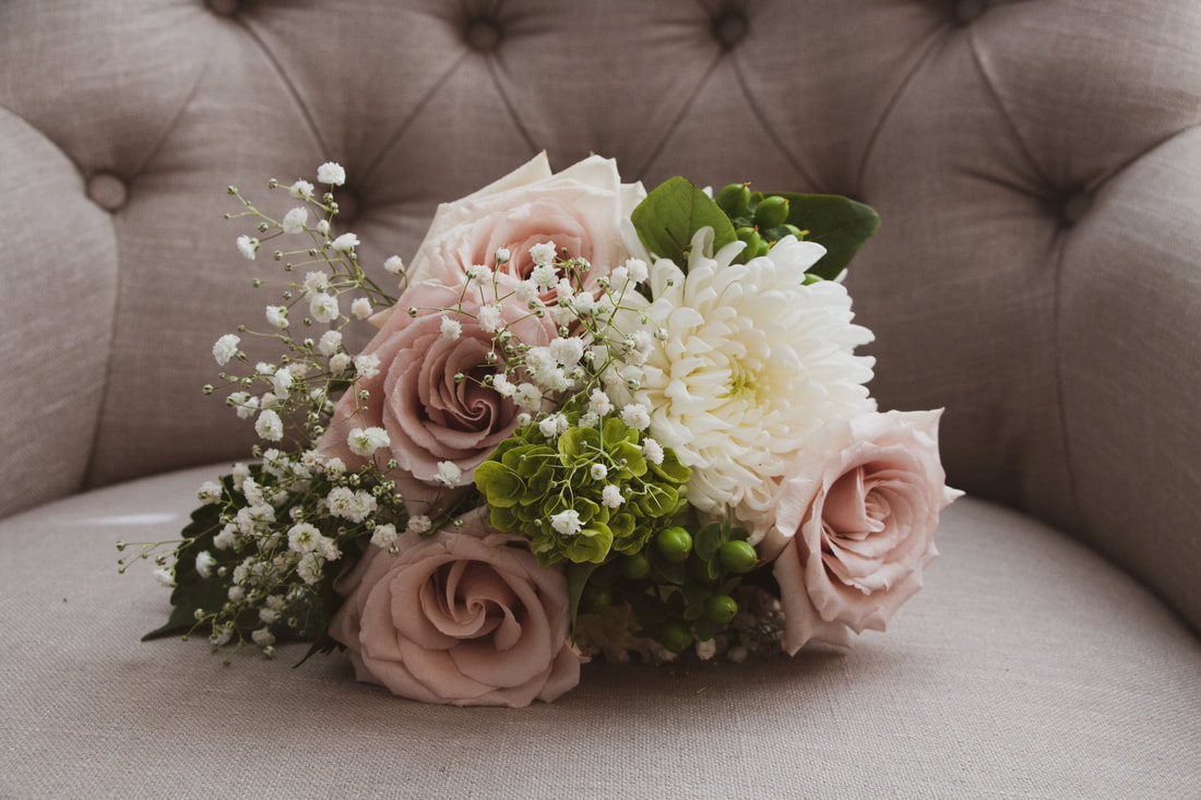 bride's blush and white bouquet on taupe chair