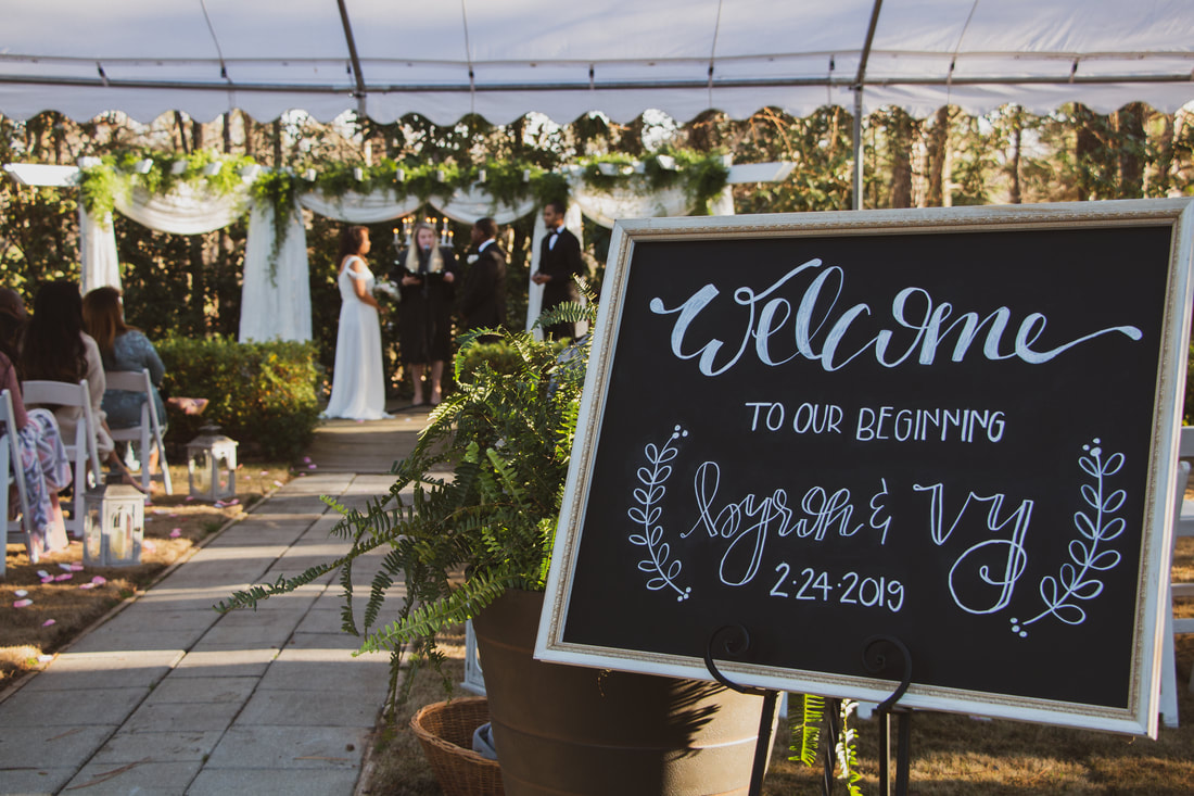 welcome chalkboard sign by ceremony area covered with a tent