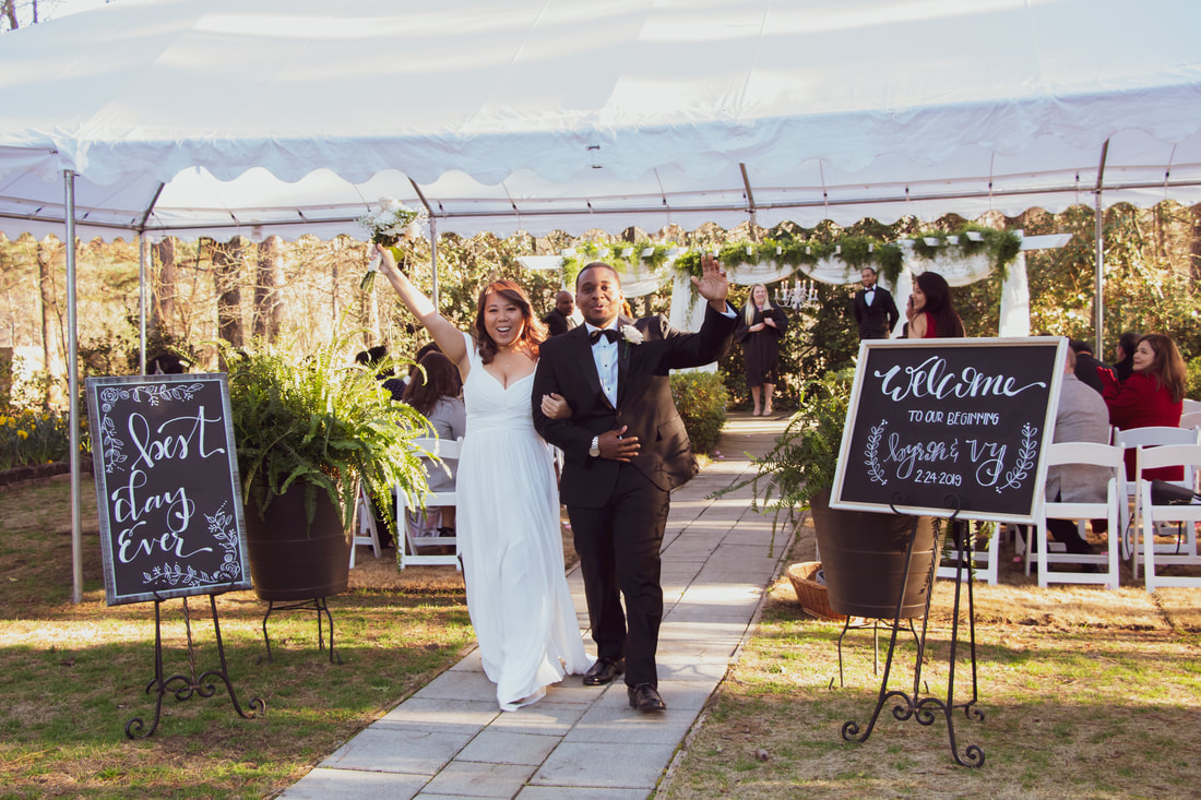 bride and groom hold up arms in celebration after February ceremony