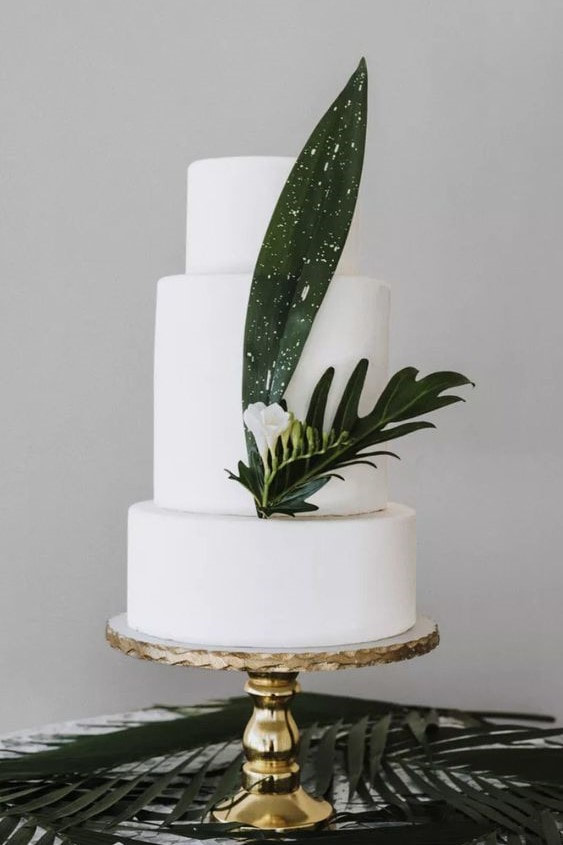 all-white wedding cake with palm leaf decor