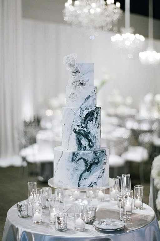 four-tiered wedding cake frosted like geodes
