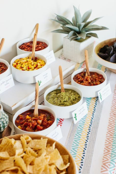 nacho bar with different salsas, guacamole, meat, and other toppings in white bowls