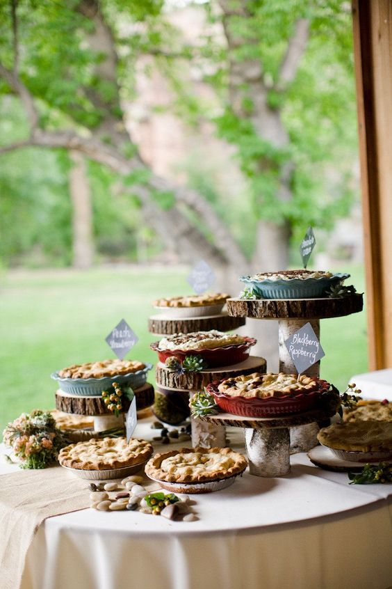 Pies on wood stands decorated with stones and flowers