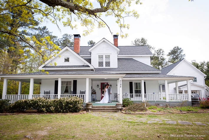 White farmhouse with a bride and groom on the porch