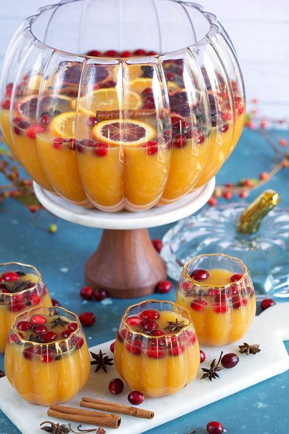 Pumpkin punch in pumpkin shaped glass bowl filled with berries, orange slices, and cinnamon sticks