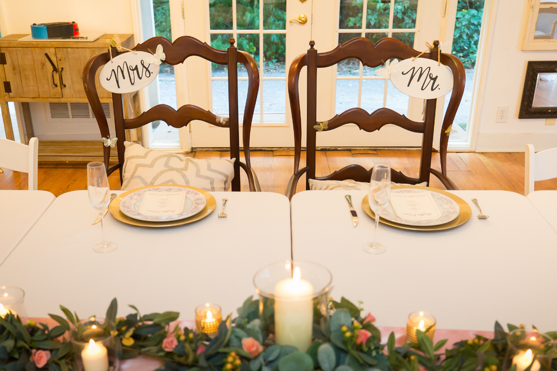 brown mr. and mrs. chairs by rehearsal dinner table setup with gold accents